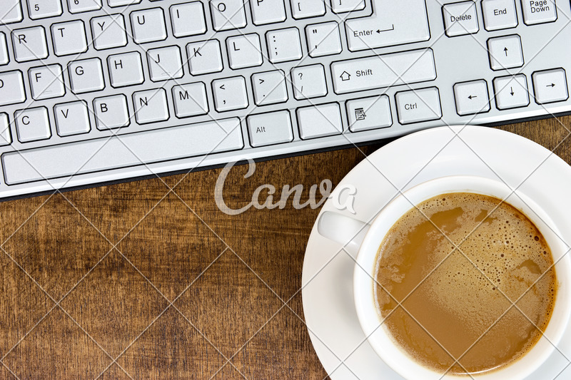 Computer keyboard and coffee cup on the wooden desk