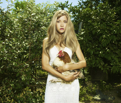 Fashion portrait of a beautiful young woman with a pet - Chicken