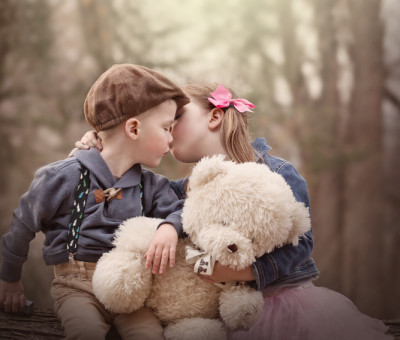 portrait of siblings sitting together outside holding a teddy bear and kissing